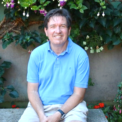 A man is sitting on a stone bench in a garden that's in bloom, smiling into the camera.